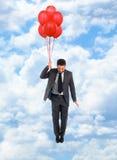 Летание бизнесмена с красными воздушными шарами Стоковая Фотография