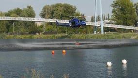 Летание вертолета спасения пожарной команды внутри, который нужно заполнить вверх с водой от реки акции видеоматериалы
