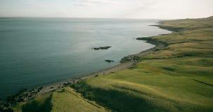 Летание вертолета вокруг побережья моря в Исландии Красивый ландшафт полей и воды лавы сток-видео