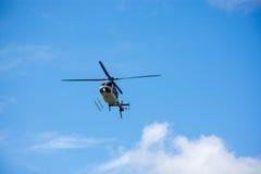 Летание вертолета через голубое небо с облаками Стоковые Изображения RF