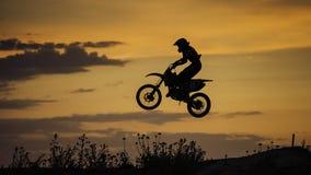 Летание велосипеда Enduro на заходе солнца Стоковые Фотографии RF