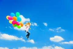 Летание маленькой девочки с красочными воздушными шарами стоковое фото