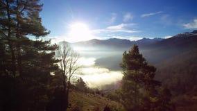 Летание между деревьями, открывающ небольшую деревню и море облаков над долиной в середине гор Восходящее солнце видеоматериал