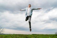 Летание молодого человека в предпосылке неба Стоковые Изображения RF