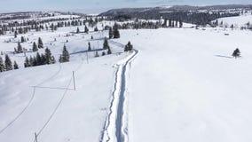 Летание над снегом покрыло дорогу в горах Воздушный фильм трутня 4k видеоматериал