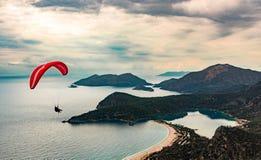 Летание параплана тандемное над пляжем и заливом Oludeniz на идилличной атмосфере Oludeniz, Fethiye, Турция Путь Lycian стоковая фотография rf