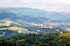Летание параплана против красивого ландшафта гор Прикарпатско, Украин Стоковые Фото