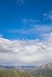 Летание птицы на голубом небе с облаками над горными пиками в Кыргызстане Стоковые Фотографии RF