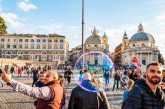 Летание пузырей мыла на Аркаде del Popolo, квадрате людей в Риме полном счастливых положительных людей, туристов и locals с римск стоковое фото rf