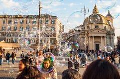 Летание пузырей мыла на Аркаде del Popolo, квадрате людей в Риме полном счастливых положительных людей, туристов и locals с римск стоковые изображения