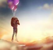 Летание ребенка на воздушных шарах стоковые изображения rf