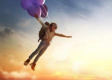 Летание ребенка на воздушных шарах стоковое изображение
