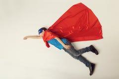 Летание ребенк супергероя Мальчик супергероя в красной накидке и голубой маске Тонизированное Copyspace, Стоковая Фотография RF