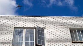 Летание самолета над домом при раскрытое окно Стоковая Фотография