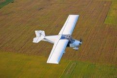Летание самолета над полями Стоковые Изображения