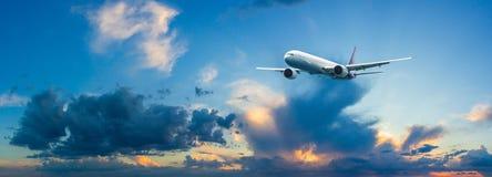 Летание самолета пассажира над облаками ночи и изумительным небом на заходе солнца стоковое фото