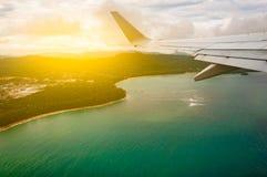 Летание самолета над островом моря пляжа голубым, принятым от окна w Стоковое фото RF