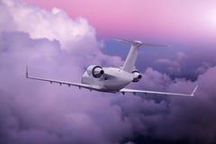 Летание самолета на фиолетовом заходе солнца над горами и морем стоковая фотография rf
