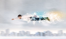 Летание супермена героя над городом с дымом вышло позади стоковые фото