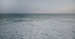 Летание трутня к большой белой пенистой океанской волне достигая берег и разбивать, создавая изумляя естественную текстуру воды видеоматериал