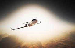 Летание частного самолета дизайна фото белое лоснистое роскошное родовое в небе под поверхностью земли Восход солнца предпосылки  Стоковое Фото