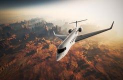 Летание частного самолета дизайна фото белое лоснистое роскошное родовое в небе под поверхностью земли Восход солнца предпосылки  Стоковое Изображение RF