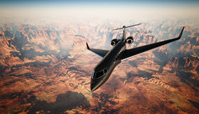 Летание частного самолета дизайна фото черное штейновое роскошное родовое в небе под поверхностью земли каньон предпосылки гранди стоковая фотография