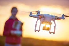 Летание quadcopter трутня на заходе солнца стоковая фотография rf