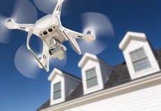 Летание Quadcopter трутня, проверяя и фотографируя дом стоковая фотография