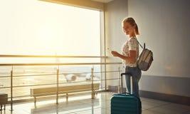 Летать молодой женщины ждать на авиапорт на окне с suitcas Стоковые Изображения RF