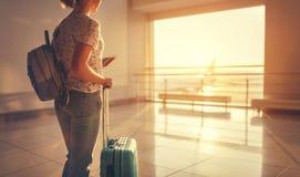 Летать молодой женщины ждать на авиапорт на окне с suitcas Стоковые Фотографии RF
