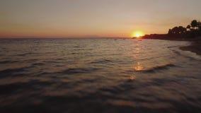 Летать над пляжем и морем с шлюпками на заходе солнца Пляж Trikorfo, Греция сток-видео