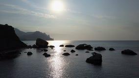 Летать ОН назад над поверхностью моря с утесами и камнями на восходе солнца Горы, утесы, камни в воде и море сток-видео