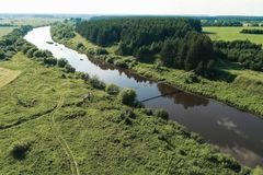 Летающ над деревней, полями, рекой и лесами Красивый взгляд s-глаза ` птицы на висеть старый мост над рекой стоковое изображение
