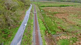 Летающ над полями, рекой и железнодорожным путем между 2 горами акции видеоматериалы