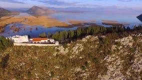 Летающ над крепостью, озером Skadar и балканскими горами в Черногории акции видеоматериалы