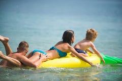 Летние каникулы и перемещение к океану Счастливые пары семьи на карибском море Отец и мать с сыном играют в воде Стоковые Изображения RF