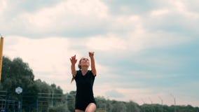 Летние каникулы, спорт и концепция людей - молодая женщина с шариком играя волейбол на пляже сток-видео