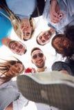 Летние каникулы, счастливые люди - группа в составе подростки смотря вниз с счастливой улыбкой на его стороне Стоковое Фото