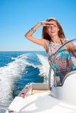 Летние каникулы - девушка управляя моторной лодкой Стоковые Изображения