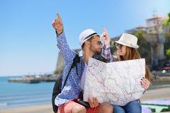 Летние отпуска, датировка и концепция туризма - усмехаясь пара в солнечных очках с картой в городе стоковые изображения