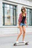 Летние отпуска, весьма спорт и концепция людей - счастливая девушка ехать современный скейтборд на улице города Стоковое Изображение