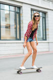 Летние отпуска, весьма спорт и концепция людей - счастливая девушка ехать современный скейтборд на улице города Стоковое фото RF