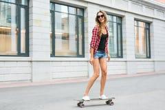 Летние отпуска, весьма спорт и концепция людей - счастливый скейтборд катания девушки на улице города Стоковые Изображения RF