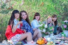 Летние отпуска и каникулы - усмехаясь девушки есть и выпивая на пляже Стоковые Фото