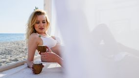 Летний отпуск на острове рая, красивых девушках в белых занавесах на бунгале, кокос в руках, видеоматериал