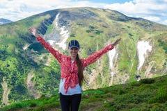 Лето в горах Молодая туристская девушка с длинными волосами в крышке с руками вверх на верхней части гор Стоковое Изображение RF