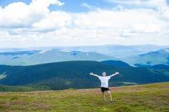 Лето в горах Молодой туристский человек в крышке с руками вверх на верхней части гор восхищает природу Стоковое Изображение