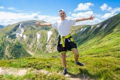 Лето в горах Молодой туристский человек в крышке с руками вверх на верхней части гор восхищает природу Стоковая Фотография