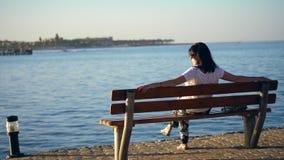 Лето, заход солнца, обваловка морем, молодая женщина брюнета сидит на стенде, задней части, восхищая красивый заход солнца сиротл сток-видео